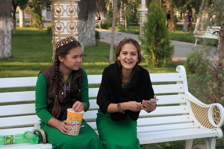 Ashgabad, Turkmenistan - October 10, 2014. Two young girls in national dress sitting on banch in park.