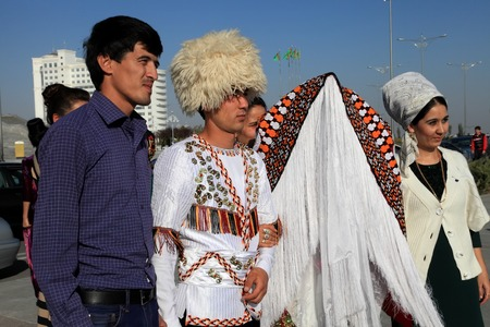 relatives: Ashgabad, Turkmenistan - October 15, 2014. The bride and groom in the Turkmen national dress, photographed with relatives.  October 15, 2014.