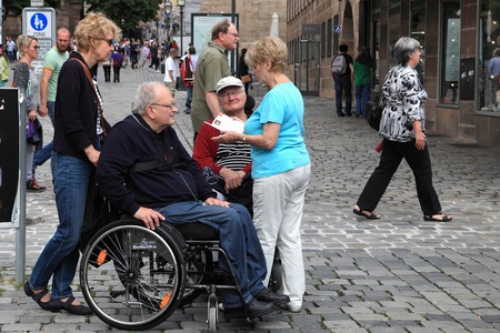 hauptmarkt: NURNBERG, GERMANY - JULY 13 2014: Tourists in wheelchairs on Hauptmarkt, the central square of Nuremberg, Bavaria, Germany.  Nuremberg accommodates annually more than 2 millions tourists Editorial
