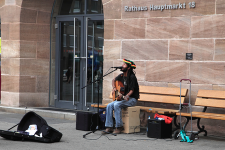 hauptmarkt: NURNBERG, GERMANY - JULY 13 2014: Hauptmarkt, the central square of Nuremberg - street musician,  singing and playing guitar ,performing at the streets Editorial