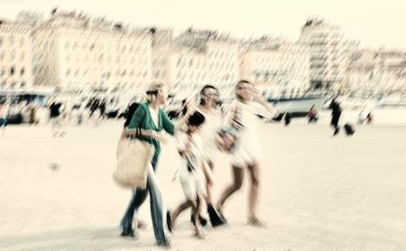 creativ: people walking along the promenade. Radial zoom blur effect defocusing filter applied Stock Photo
