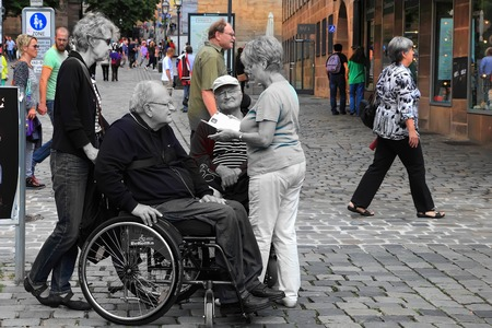 christkindlesmarkt: NURNBERG, GERMANY - JULY 13 2014: Tourists in wheelchairs on Hauptmarkt, the central square of Nuremberg, Bavaria, Germany.  Nuremberg accommodates annually more than 2 millions tourists Editorial