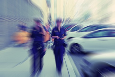Abstract background. Two female police officers walking along the streets of Vienna in Austria. Radial zoom blur effect defocusing filter applied