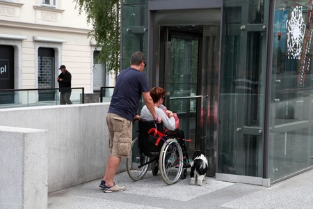 come in: LJUBLJANA, SLOVENIA -  JUNE 28, 2014: Husband and wife in a wheelchair with a dog come in passenger lift. LJUBLJANA, JUNE 28, 2014