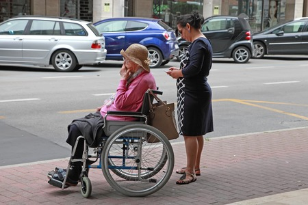 oldage: VENICE, MESTRE-June 29, 2014:  Young woman pushing a old woman in a wheelchair.  VENICE, MESTRE-June 29, 2014.  Mestre is the most populated urban area of the mainland of Venice, part of the territory of the city of Venice, in Veneto, Italy.