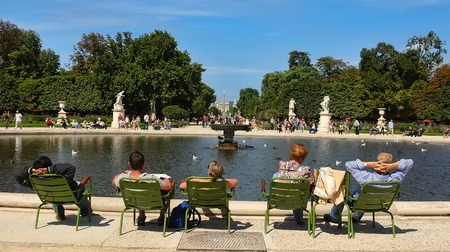 city park: PARIS, FRANCE - August 19, 2014: Tourist and and Parisians rest in Tuileries garden near Louvre museum. Created by Catherine de Medicis, it became a public park after the French Revolution.