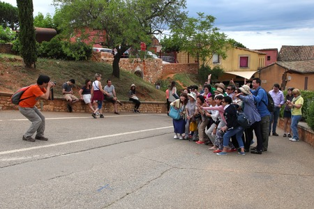 roussillon: ROUSSILLON, FRANCE - JULY 07, 2014: A group of tourists photographed against the backdrop of the  medieval village of Roussillon. Roussillon ocher village is included in list of The most beautiful villages of France