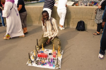 immigrant: Paris, France August 18 2014. African immigrant offering souvenirs on a bridge over the Seine. Paris, France August 18 2014