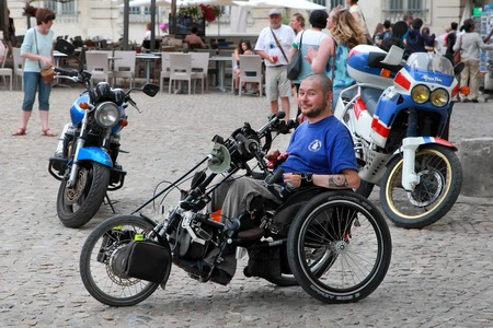 1 person: France, Avignon - July 1, 2014. Young man disabled person sits in a wheelchair. Aix-en-Provence is a part of the cultural and historical heritage of France.  Aix-en-Provence, JULY 1, 2014. Editorial