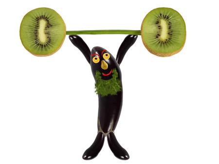 raises: Creative food concept. Funny eggplant raises the bar of kiwi. Stock Photo
