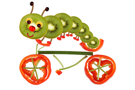 children eating: Creative food concept. Funny little caterpillar on a bicycle made from fruit and vegetables