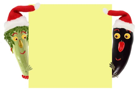 kids eating: Creative food concept. Funny small zucchini and eggplant in a Santa Claus hat look and smile with sample text. Stock Photo