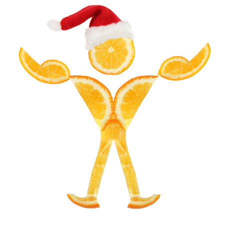 Healthy eating. Funny little man in Santa Claus hat made of the orange slices Stock Photo