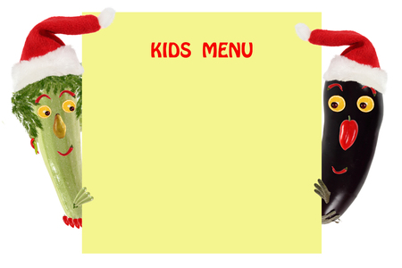 sample text: Creative food concept. Funny small zucchini and eggplant in a Santa Claus hat look and smile with sample text. Stock Photo