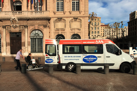 wheelchair users: France, Marseille -November 19, 2015: Driver helping man on wheelchair getting into municipal transport for wheelchair users. MARSEILLE -November 19, 2015.