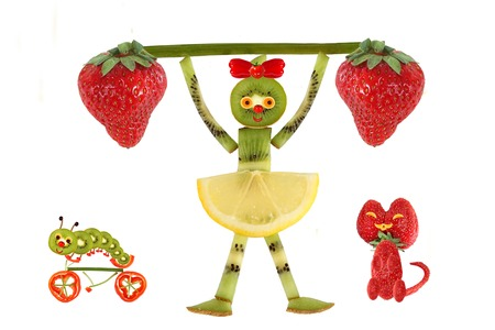 children eating: Creative food concept. Funny little girl  with slices of kiwi.