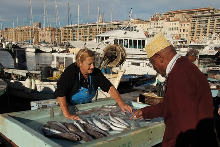 city fish market: France, Marseille -November 19, 2015: The buyer at the fish market in Marseille.  Old Port of Marseille (Vieux-Port), Marseille is Frances largest city on the Mediterranean coast and largest commercial port. October 19, 2015.