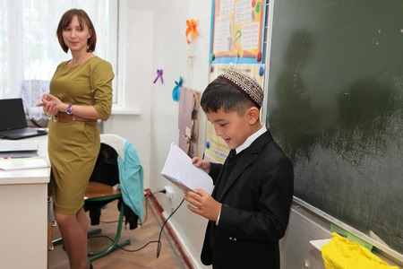 narrate: Ashgabad, Turkmenistan - November 4, 2014. Schoolboy telling lesson at the blackboard. November 4, 2014.  In schools of Turkmenistan annually trains about 900 thousand children. Editorial