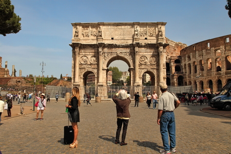 constantino: ROMA, ITALY, APRIL 7, 2016 : Tourists visiting Arco de Constantino (Arch of Constantine) and Colosseum. The arch was erected by the Roman Senate to commemorate Constantine victory over Maxentius