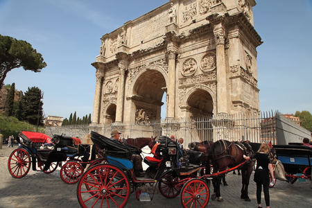 ROMA, ITALY, APRIL 7, 2016 : Coachman sits on a carriage, pulled by a horse, waiting for tourists. Arco de Constantino (Arch of Constantine) and Colosseum. The arch was erected by the Roman Senate to commemorate Constantine victory over Maxentius Stock Photo