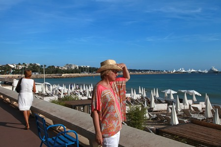 CANNES, FRANCE -  JULY 5, 2015. Woman looking at the sea, on Croisette promenade in Cannes, France. Cannes located in the French Riviera. The city is famous for its Film Festival. CANNES, FRANCE -  JULY 5, 2015: Editorial