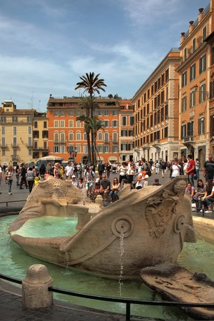 ROME, ITALY - APRIL 7, 2016: Piazza di Spagna - popular meeting places in Rome. Fontana della Barcaccia - elegant looking fountain commissioned by pope Urban VIII, designed by Gian Lorenzo Bernini.
