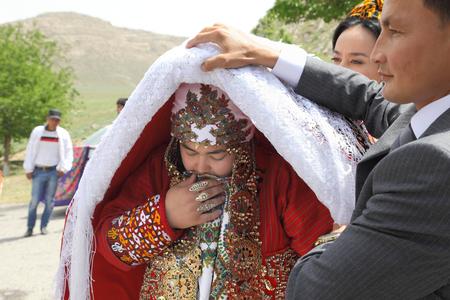 Kov-Ata, Turkmenistan - April 30, 2017: Turkmen national wedding in the village of Kov-Ata. The groom shows his brides face to the guests.  Turkmenistan - April 30, 2017. Redakční