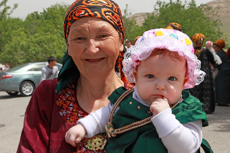 Kov-Ata, Turkmenistan - April 30, 2017: Grandmother with her granddaughter at a national wedding in the village of Kov-Ata. Turkmenistan - April 30, 2017. Redakční