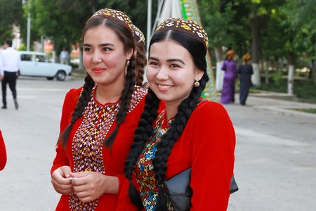 Ashgabat, Turkmenistan - May 25, 2017: Group of smiling female students in red national dresses with embroidery. Ashgabat, Turkmenistan, May 25, 2017. Editorial