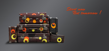 Shabby Vintage Ancient Suitcases. Concept travel with the inscription Start now Not tomorrow! on a dark background.