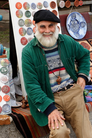 Chisinau, Moldova- April, 03, 2010.  Portrait of an unknown artist  at the open air artist market. In the background of the artists work. Chisinau, Moldova- April, 03, 2010.