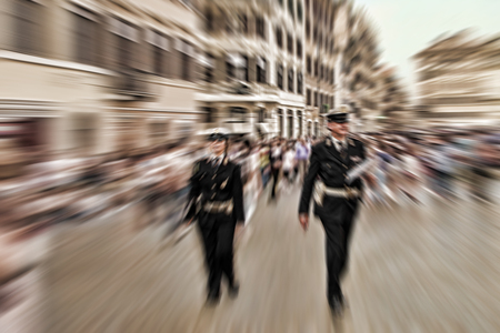 Abstract background. Two  police officers walking along the streets of Rome, Italy. Radial zoom blur effect defocusing filter applied
