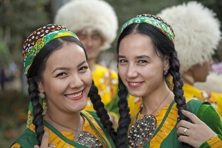 September, 3, 2017. Ashgabat, Turkmenistan : Two smiling young girls in green national dresses before the performance at the Kurban-Bairam Festival. September, 3, 2017. Ashgabat