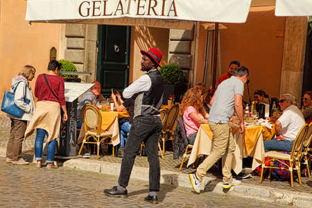 ROME, ITALY - APRIL 11, 2018: People enjoy their lunch at one of the many restaurants in Navona Square, Rome