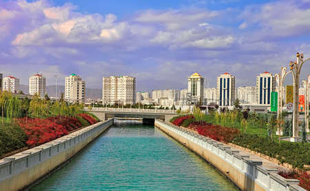 Ashgabat, Turkmenistan - September 26, 2017: Modern architecture of Ashgabat. New apartamentes behind a young park with fountain complex. Ashgabat is the capital of Turkmenistan.