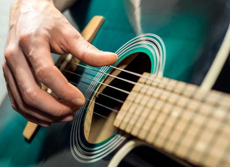 guitarra acustica: Un Hombre que juega en la guitarra acústica