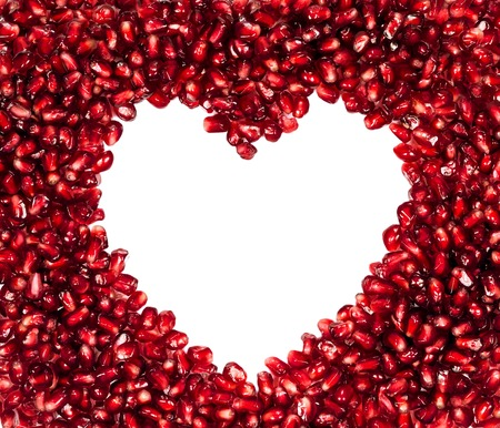 Fresh pomegranate seeds in a heart-shaped isolated on a white background