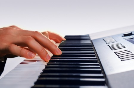 man playing on a synthesizer, isolated on a gradient gray background photo