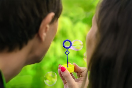 portrait of young couple having fun with soap bubbles in the park 版權商用圖片