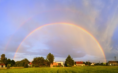 Rainbow at sunset over the village in Poland