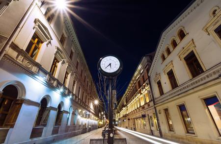 Antique clock on Piotrkowska Street, Lodz, Poland in the evening.