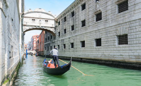 Gondolier punting gondola through green canal waters of Venice. Italy. Europe.