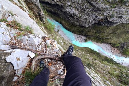Tourist's feet on a precipice, area of Villanova. Belluno. Italy