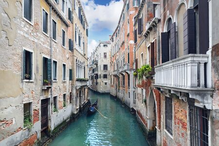Gondolier punting gondola through green canal waters of Venice. Day foto. Italy. Europe.