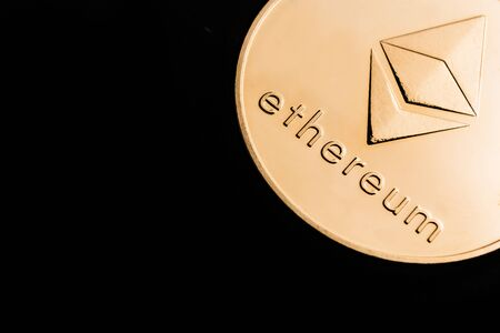 Gold cryptocurrency coin - Etherum, isolated on a black background.