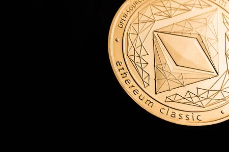 Gold cryptocurrency coin - etherum classic, isolated on a black background. Stock fotó