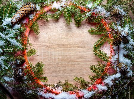 Christmas round frame made by neon and winter things on wood background.