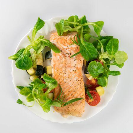 Delicioso pescado asado servido en plato blanco Foto de archivo