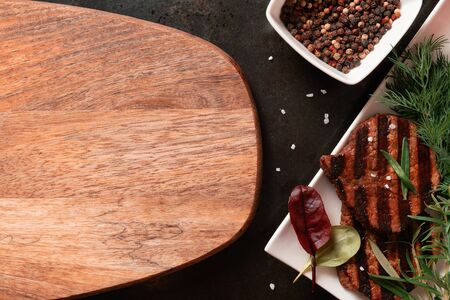 Food background, two grilled beef steaks, spices herbs. Flat lay top view copy space, wooden background Banco de Imagens