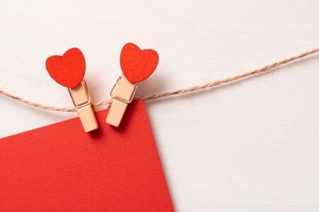 lovers symbol. Clothes pegs with red wooden hearts. 스톡 콘텐츠